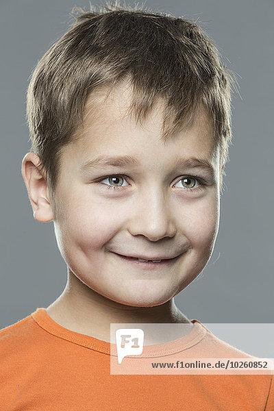 Lächelnder Junge schaut weg vor grauem Hintergrund