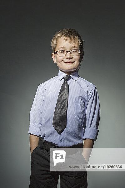 Porträt eines gut gekleideten Jungen vor grauem Hintergrund