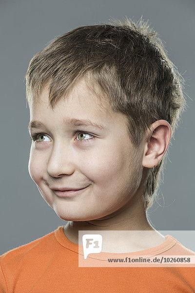 Nahaufnahme des lächelnden Jungen vor grauem Hintergrund