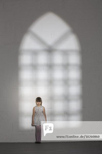 Schatten des Fensters  das auf ein Mädchen fällt  das zu Hause an der weißen Wand steht.