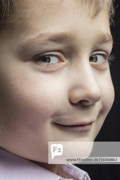 Nahaufnahme des lächelnden Jungen vor schwarzem Hintergrund