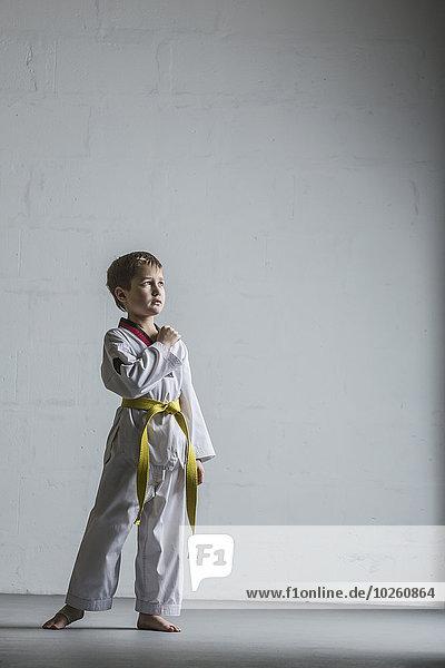 Volle Länge des Karatejungen an der weißen Wand stehend