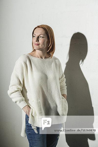 Nachdenkliche Frau stehend mit Händen in Taschen vor weißem Hintergrund