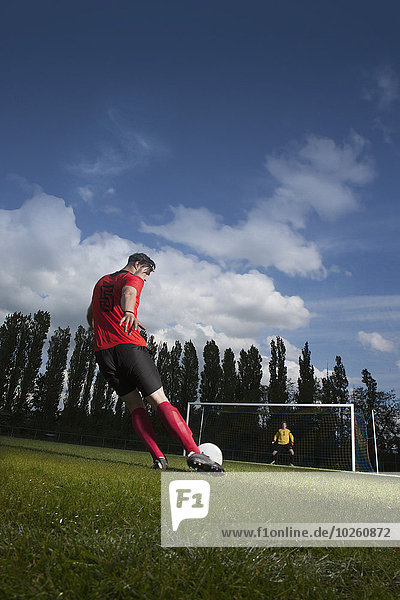 Volle Länge des Fußballspielers  der den Ball am Tor kickt.