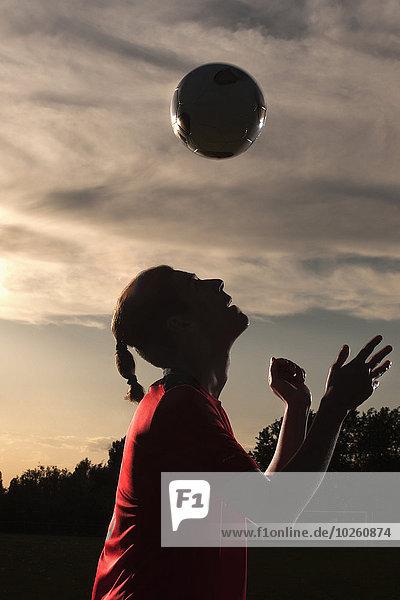 Seitenansicht des Fußballspielers mit Kopfball im Feld