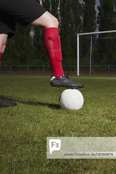 Niedriger Bereich des Fußballspielers mit Fuß auf Ball vor dem Torpfosten