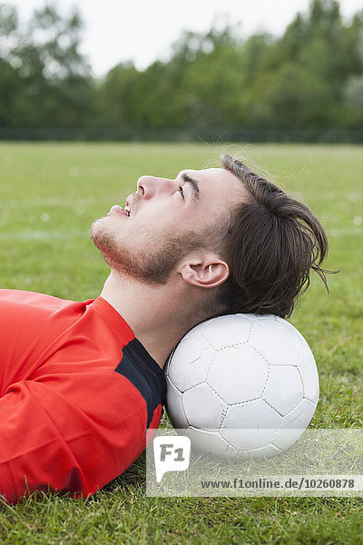 Seitenansicht des jungen Mannes  der den Kopf auf dem Fußballfeld ausruht.