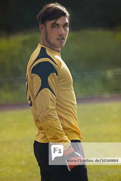 Sicherer Fußballspieler schaut weg  während er auf dem Spielfeld steht.