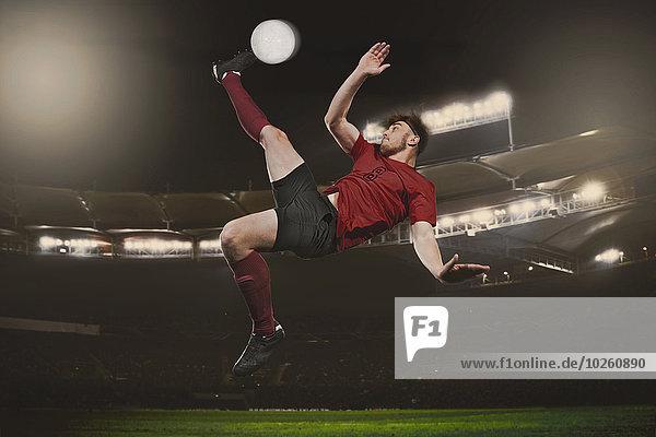 Volle Länge des Fußballspielers  der den Ball auf dem Spielfeld kickt.