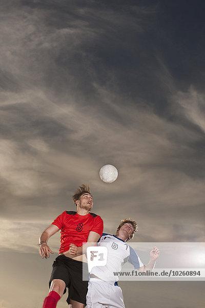 Männliche Fußballspieler beim Ball gegen den Himmel