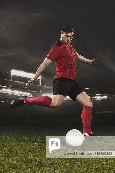 Volle Länge des jungen Fußballspielers  der den Ball auf dem Spielfeld kickt.