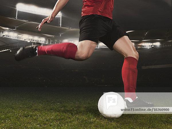 Niedriger Abschnitt eines jungen Fußballspielers  der den Ball auf dem Spielfeld kickt.