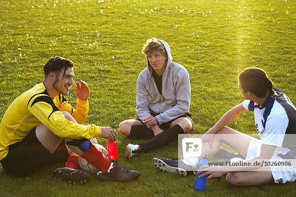 Junge Fußballspieler entspannen sich auf dem Spielfeld