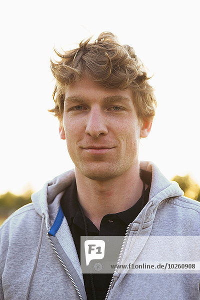 Porträt eines selbstbewussten jungen Fußballspielers mit Kapuzenjacke im Freien