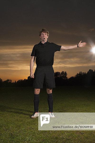 Schiedsrichter-Signalisierung beim Pfeifen auf dem Fußballfeld