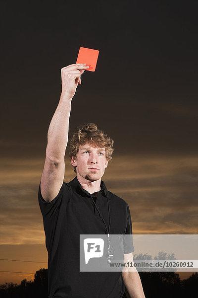 Junger Fußballschiedsrichter mit roter Karte bei Sonnenuntergang