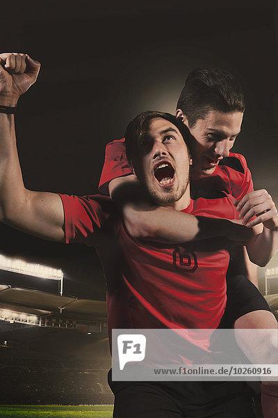 Männliche Fußballspieler feiern Sieg im Stadion