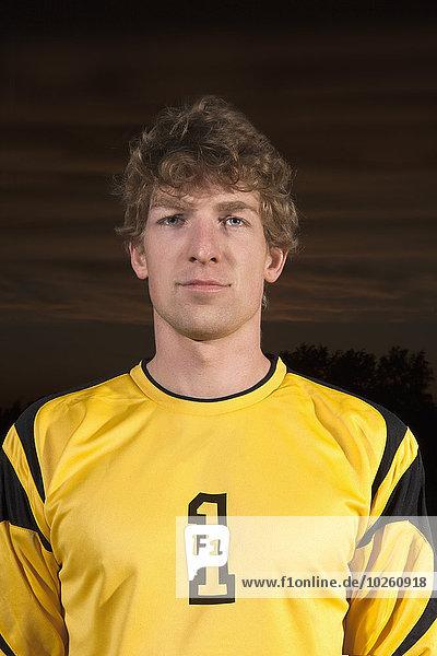 Porträt eines selbstbewussten Fußballtorhüters auf dem Spielfeld bei Nacht