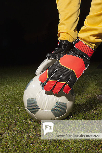 Abgeschnittenes Bild eines jungen männlichen Torhüters  der einen Fußball auf dem Spielfeld platziert.