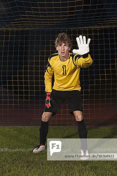 Porträt eines selbstbewussten Torhüters  der das Fußballnetz auf dem Spielfeld verteidigt.