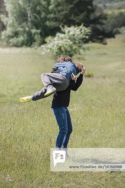 Volle Länge der verspielten Mutter  die den Sohn auf dem Rasen trägt.