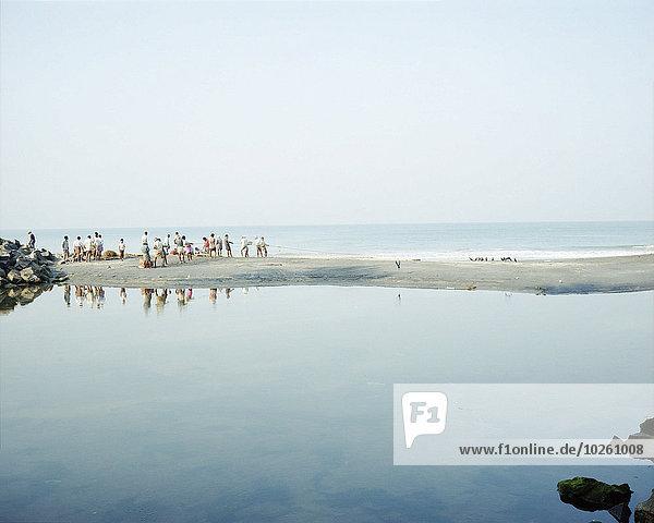 Menschen auf der Sandbank inmitten des Meeres gegen den klaren Himmel