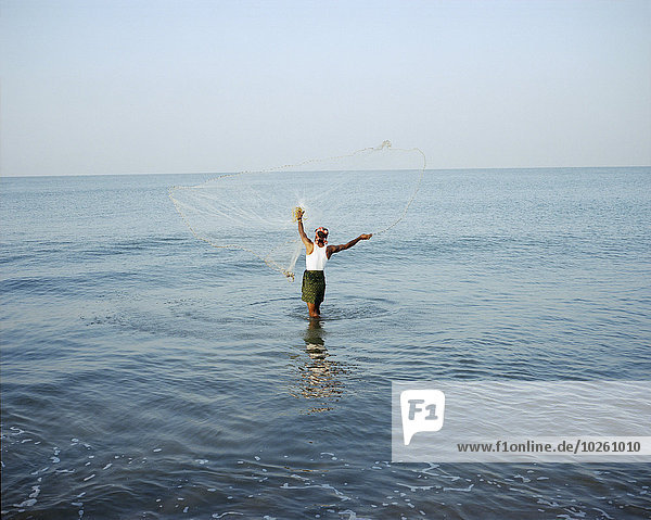 Rückansicht des Mannes  der das Fischernetz auf See gegen den klaren Himmel wirft.