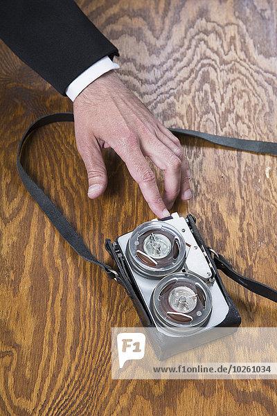 Beschnittenes Bild eines Geschäftsmannes mit altmodischem Tonbandgerät auf Holztisch