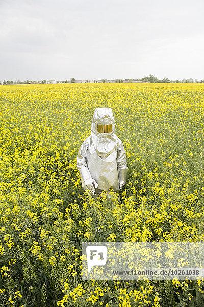 Eine Person in einem Strahlenschutzanzug  die in einem Rapsfeld steht.