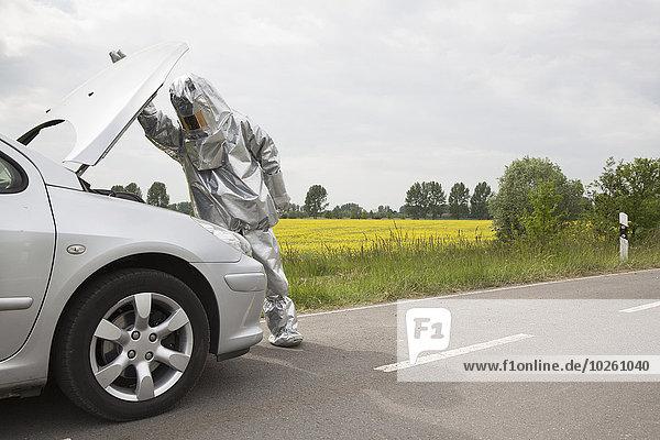 Eine Person in einem Strahlenschutzanzug  die unter die Motorhaube eines Autos schaut.