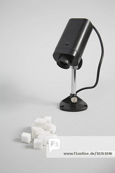 Sicherheitskamera und Zuckerwürfel vor weißem Hintergrund