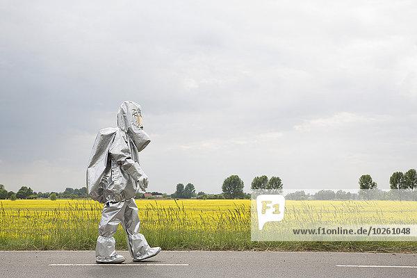 Eine Person in einem Strahlenschutzanzug  die an einem Rapsfeld entlanggeht.