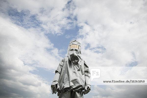 Eine Person in einem Strahlenschutzanzug  die gegen einen bewölkten Himmel steht.