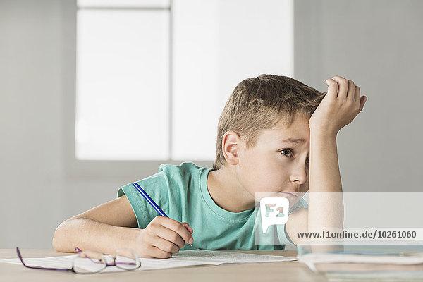 Gelangweilter Junge mit Hand auf der Stirn beim Hausaufgaben machen