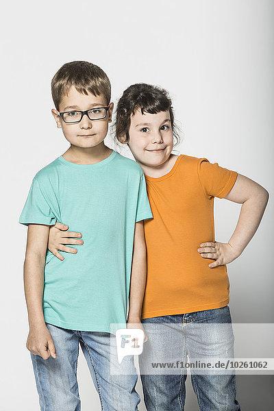 Porträt von Geschwistern  die auf weißem Hintergrund stehen