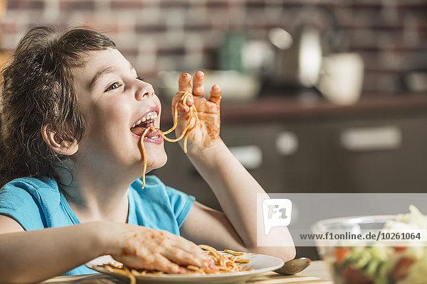 Fröhliches kleines Mädchen  das zu Hause Spaghetti mit den Händen isst.