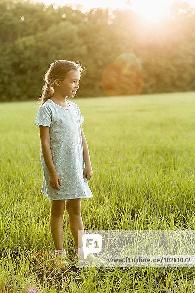 Volle Länge des fröhlichen Mädchens auf dem Grasfeld stehend