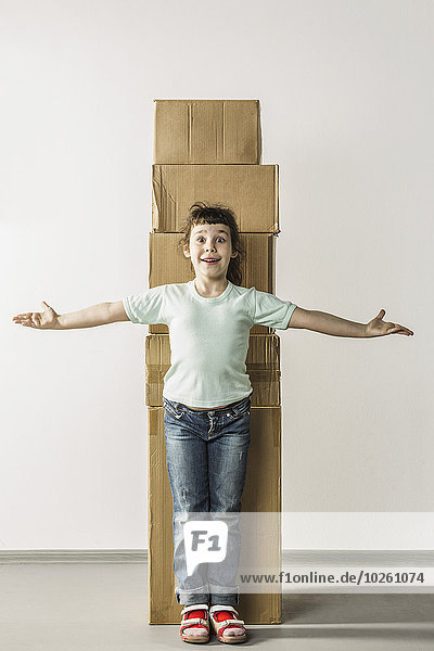 Portrait des überraschten Mädchens mit ausgestreckten Armen an gestapelten Kisten stehend