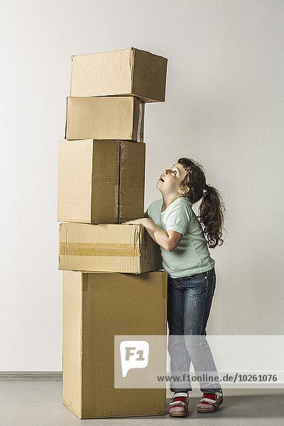 Volle Länge der Girl-Balancing-Stapelboxen im Haus