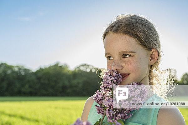 Glückliches Mädchen riecht lila Blumen auf dem Feld