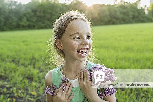 Fröhliches Mädchen mit lila Blumen auf dem Feld