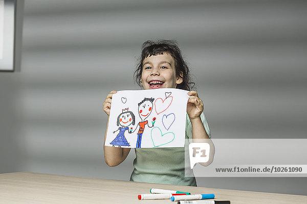 Lächelndes Mädchen zeigt Malerei zu Hause