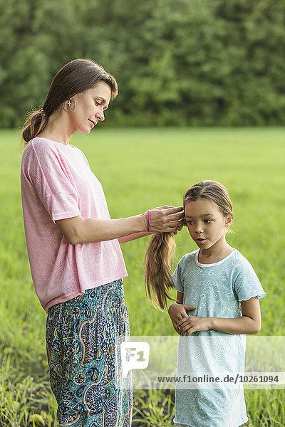 Mutter macht die Haare der Tochter auf dem Feld