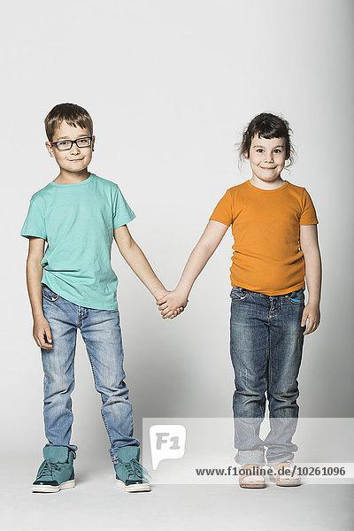 Ganzflächiges Porträt von Geschwistern auf weißem Hintergrund