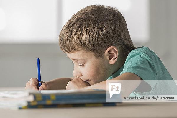 Seitenansicht des Jungen bei den Hausaufgaben zu Hause