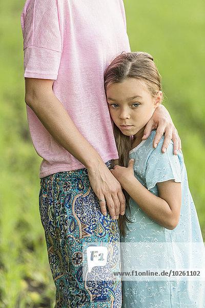 Trauriges Mädchen umarmt Mutter auf dem Feld