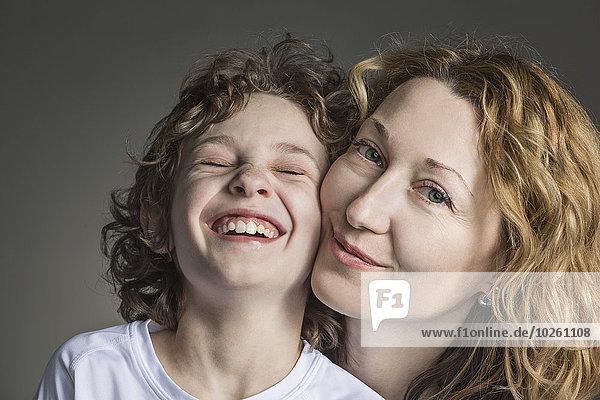 Nahaufnahme von Mutter mit fröhlichem Sohn über grauem Hintergrund