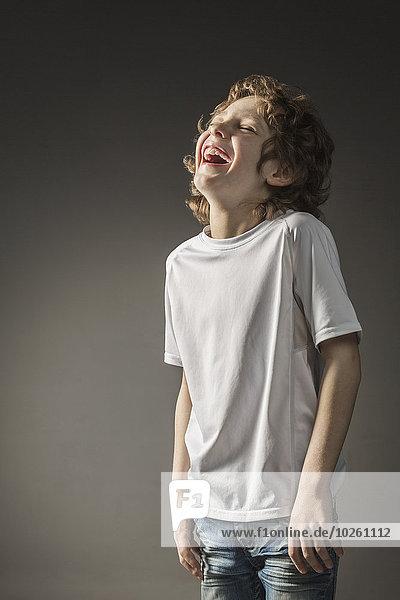 Junge lacht über grauen Hintergrund