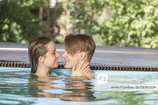 Seitenansicht eines leidenschaftlichen Paares  das im Schwimmbad lächelt.