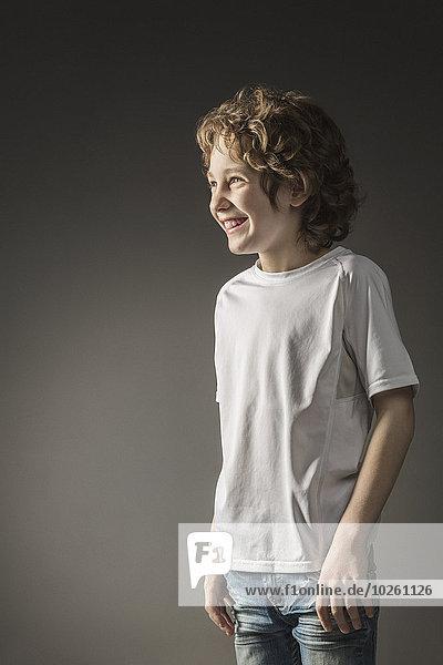 Junge lächelt  während er über den grauen Hintergrund schaut.